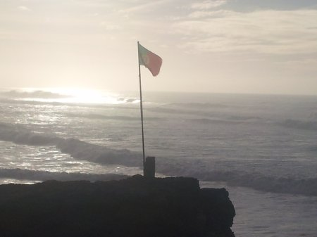 The greatest show on earth: a lone flag flutters over the groundswell on Portugal's west coast.