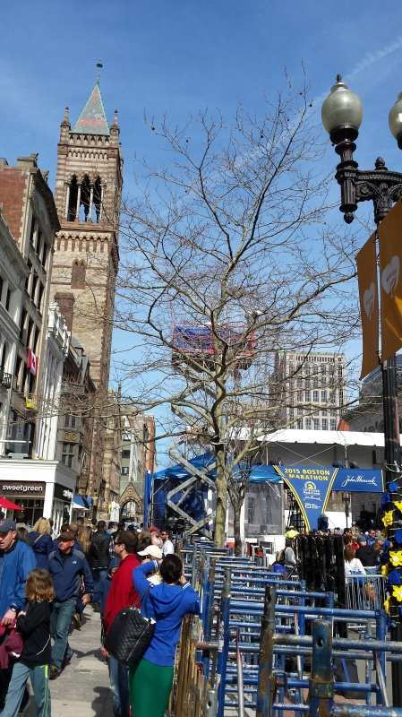The 2015 Boston Marathon. The downtown  area is packed to capacity, preparing to receive thirty thousand runners—America responds in style to last year's terrorist attack.