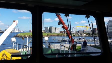 Belfast Harbor seen from the upper deck of a converted trawler. The Titanic Odyssey building is directly in front, and the famous Harland and Wolff gantry is on the right. Two gantries, Samson and Goliath are now used for shipbuilding.